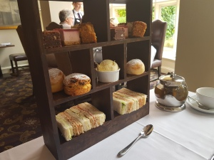 Sandwiches, scones, cream and jam, and cake cubes on a dark-wood stand.