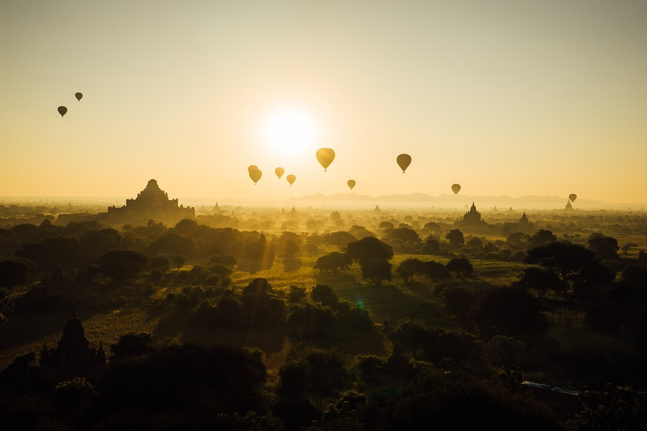 Hot-air balloons over yellow/green countryside, with yellow light from sun