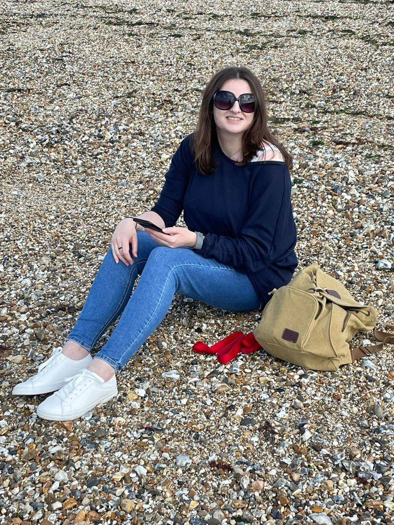 The author (long brown hair, sunglasses, blue jumper, blue jeans, white trainers) sitting on a pebble beach